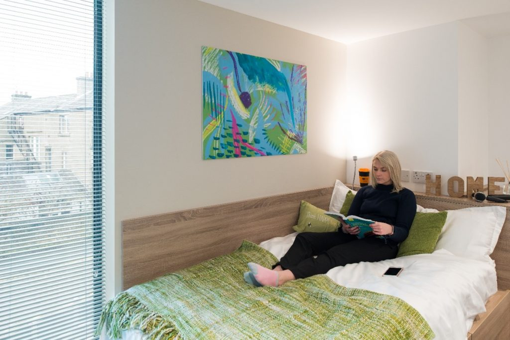 women, reading book in her accommodation, in bed